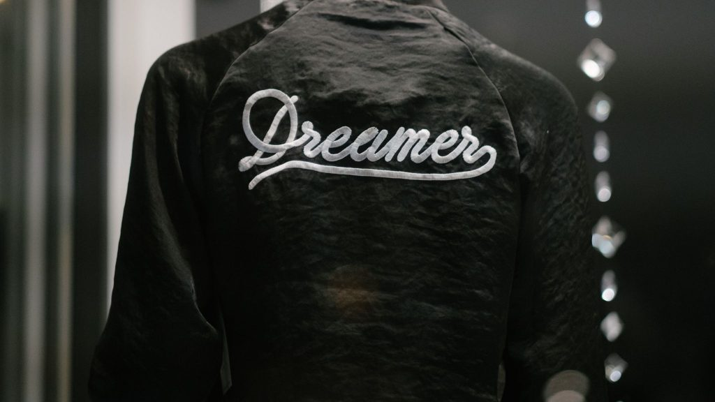 "Back of black jacket with the words""Dreamer"" embroidered on it in white thread"