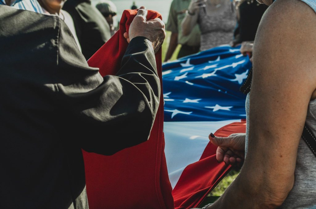 park visitors folding american flag at park closing nightly ceremony